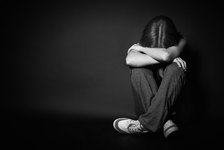 sad woman in depression and despair crying on black dark background